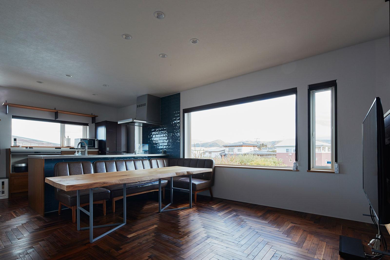 1枚板のテーブルに大きな窓。キッチン奥の窓からも陽が射して明るい2階の子世帯のリビング