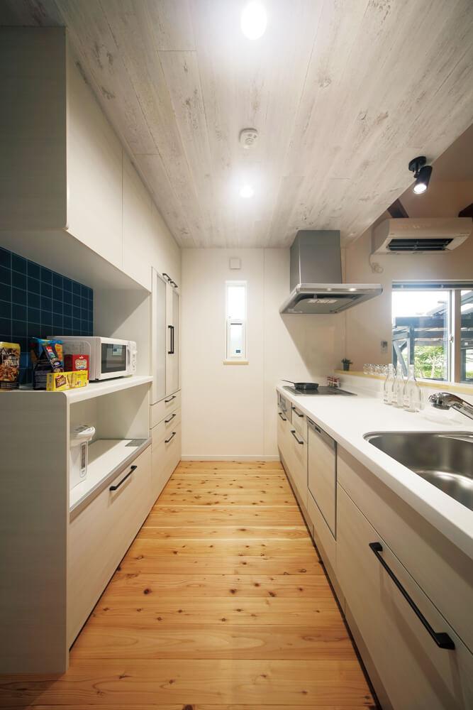 ゆったりとした幅で動きやすいキッチン。天井には白くペイントしたオーク柄の突板をあしらった