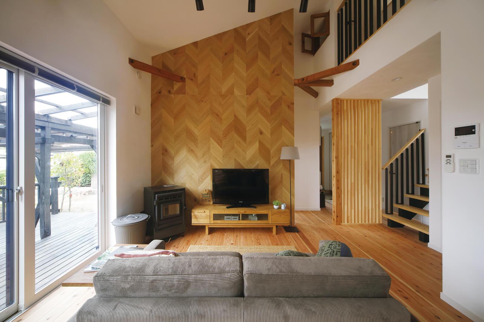 勾配天井が印象的なリビング。奥の壁にはラスティックな趣漂うヘリンボーン柄のリアルパネルを施工した