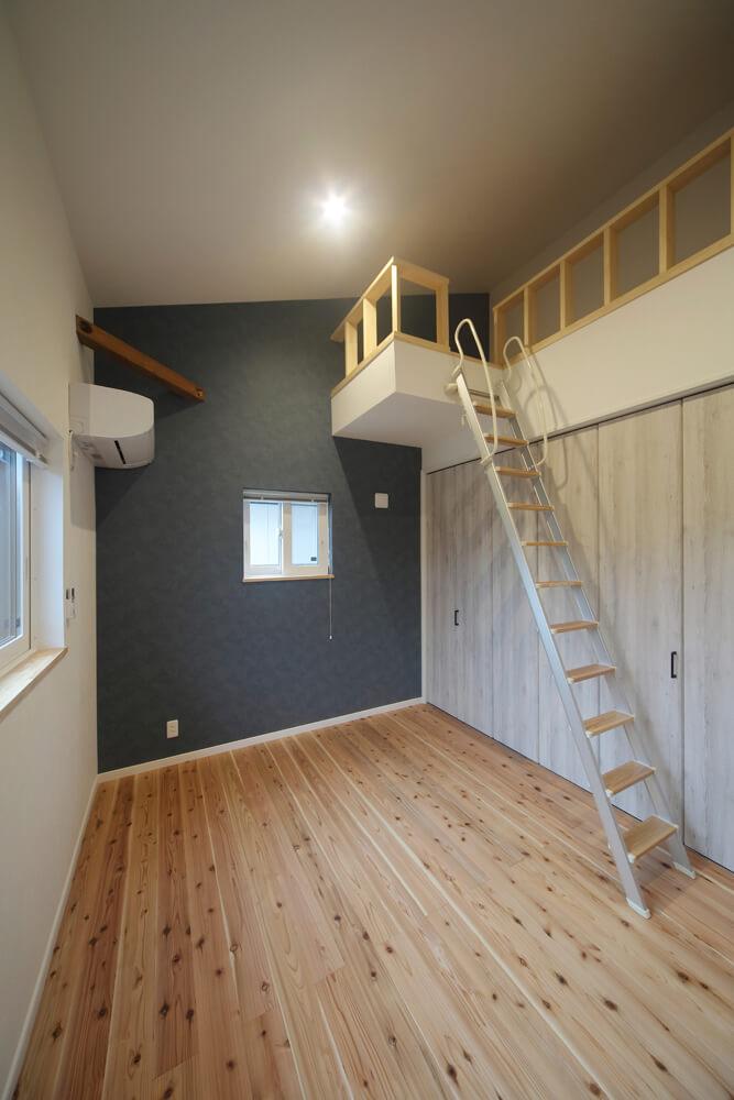 ブルーグレー系のアクセントクロスが映える1階の寝室。寝室にも、勾配天井を生かしたロフトスペースが設けられている