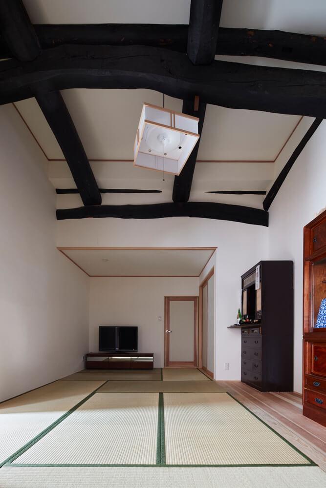 もとからあった太鼓梁を現しにした9.5畳の和室。奥の扉は祖父母の住む隣の別棟へとつながっている