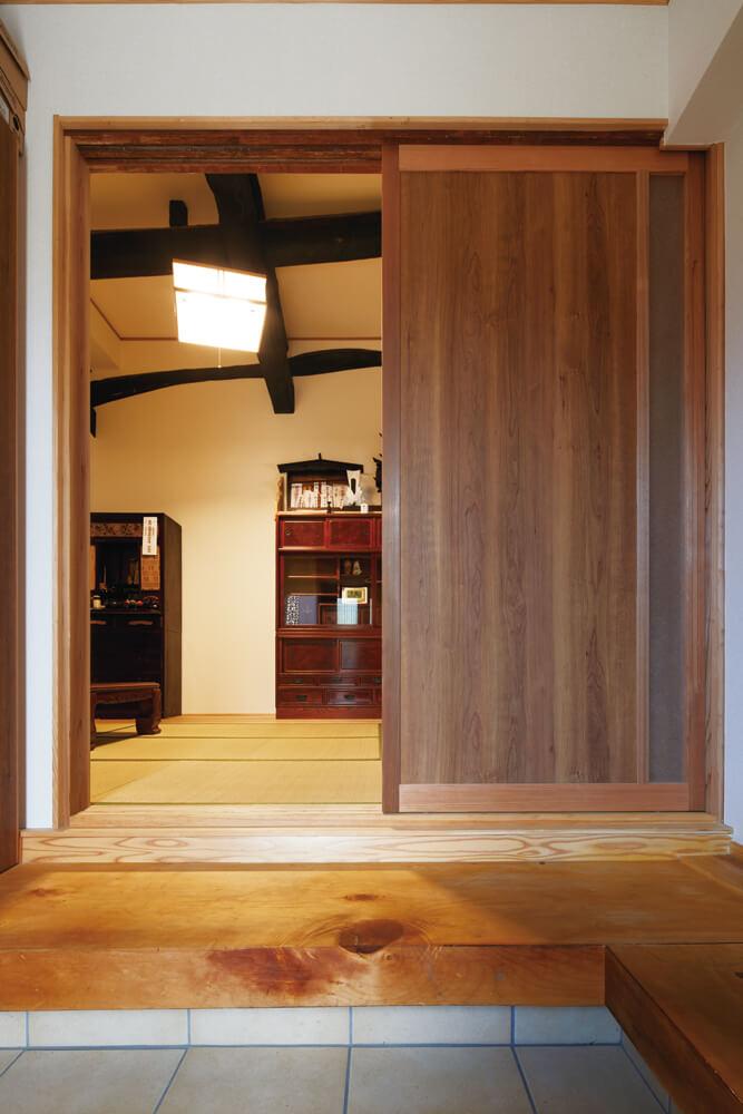 玄関からこの家の顔ともいえる和室の梁が見渡せる。玄関の上がり框の木も前の家で使われていたもの