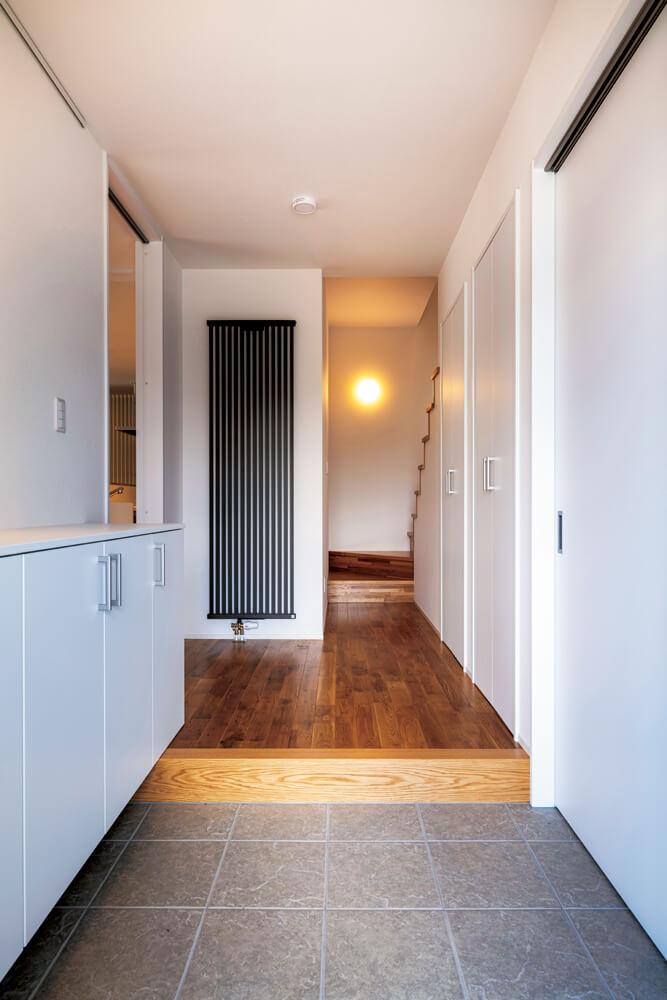 玄関を入ると、グレーのパネルヒーターが視界に入る。室内のカラーや雰囲気に合わせて選べばインテリアの一部に