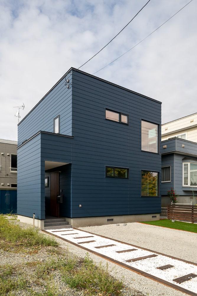 シンプルなネイビーのガルバリウム鋼板張りの外観。玄関アプローチには白砂利と木でお洒落にアレンジ