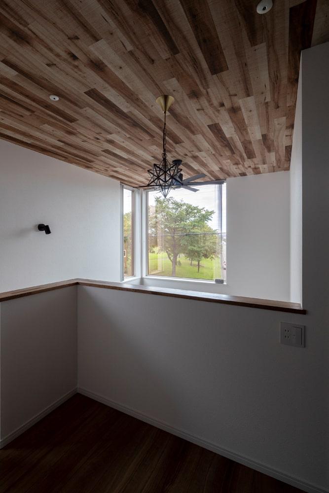 吹き抜け部分の天井は木調のクロスを貼って、2階の踊り場にはデザインライトを。夜には外から灯りが見える