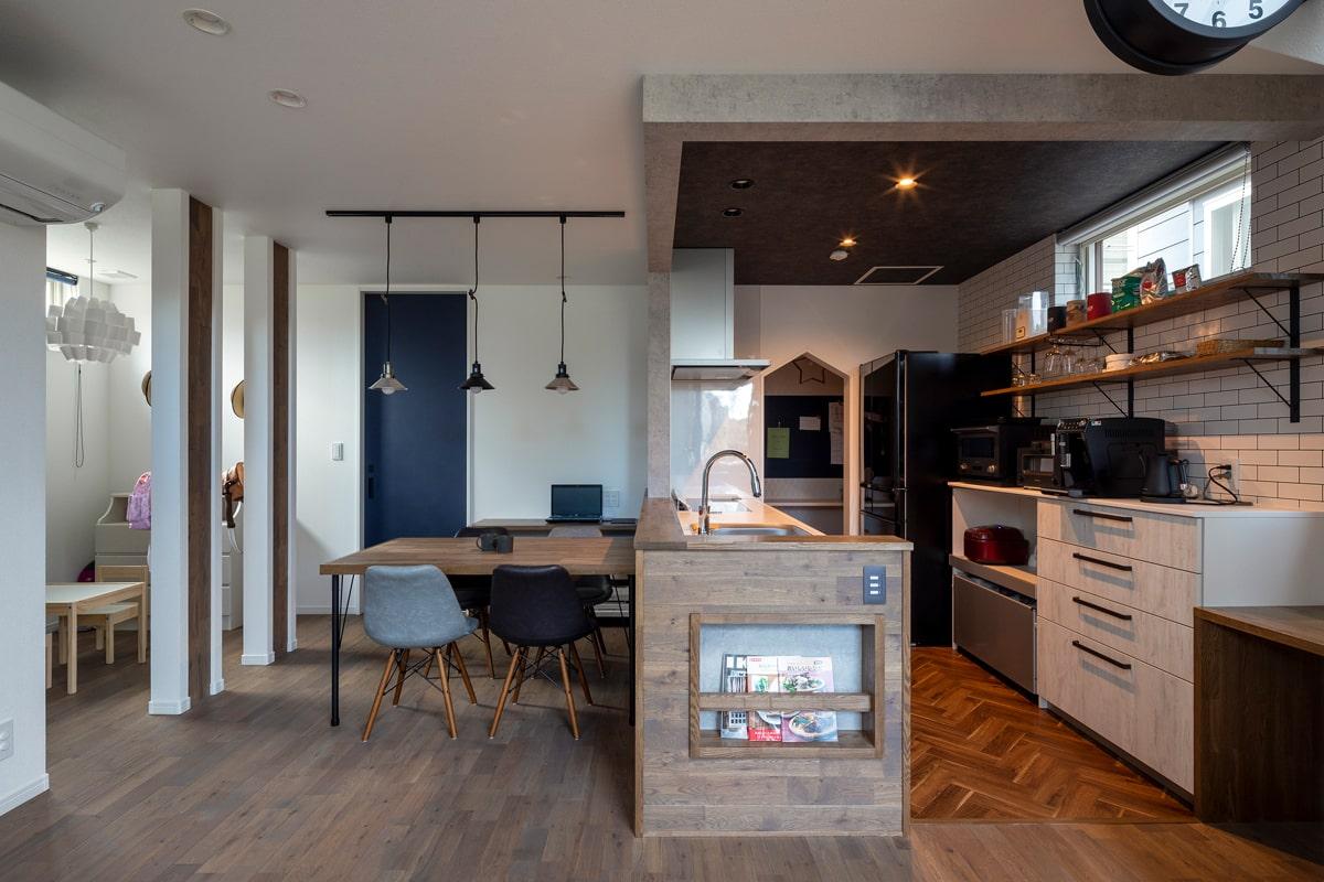 キッチンカウンターの側面は床と同じ無垢板張り。ダイニングの左には子どもの学習スペースを設けた