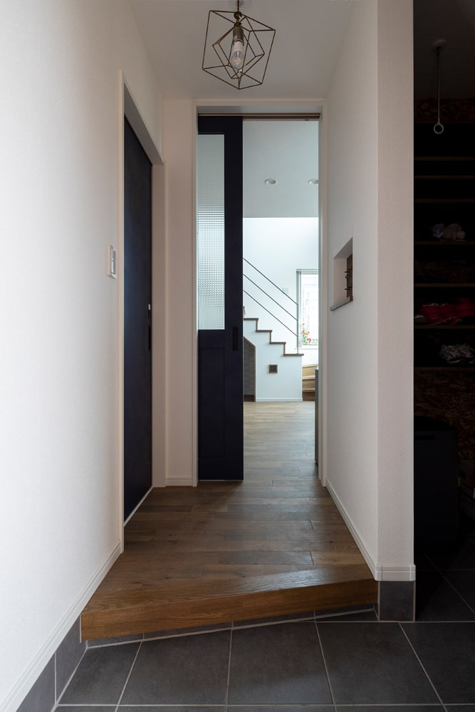 玄関とLDKの間の扉は、中の様子がさりげなく伺えるすりガラスに。土間右手には家族用のシューズクローゼット