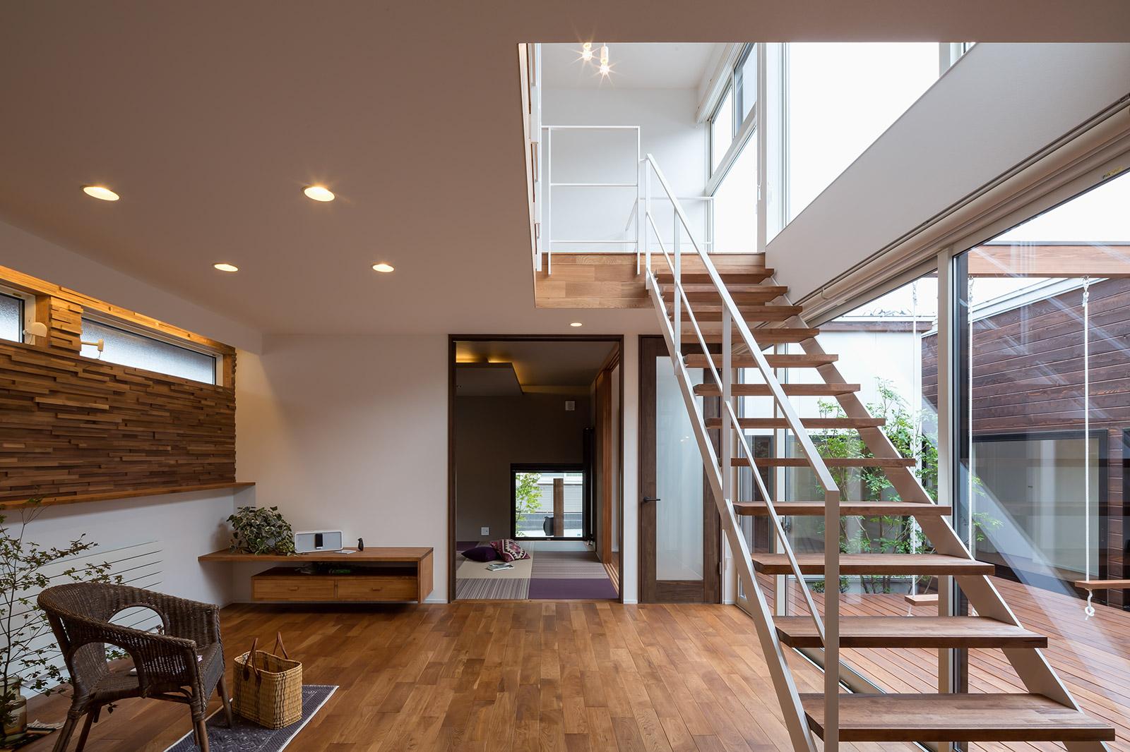 親世帯のリビングと和室(奥)。視線が遠くまで広がるオープンな空間構成で、窓配置の工夫と中庭からの光で十分明るく開放的