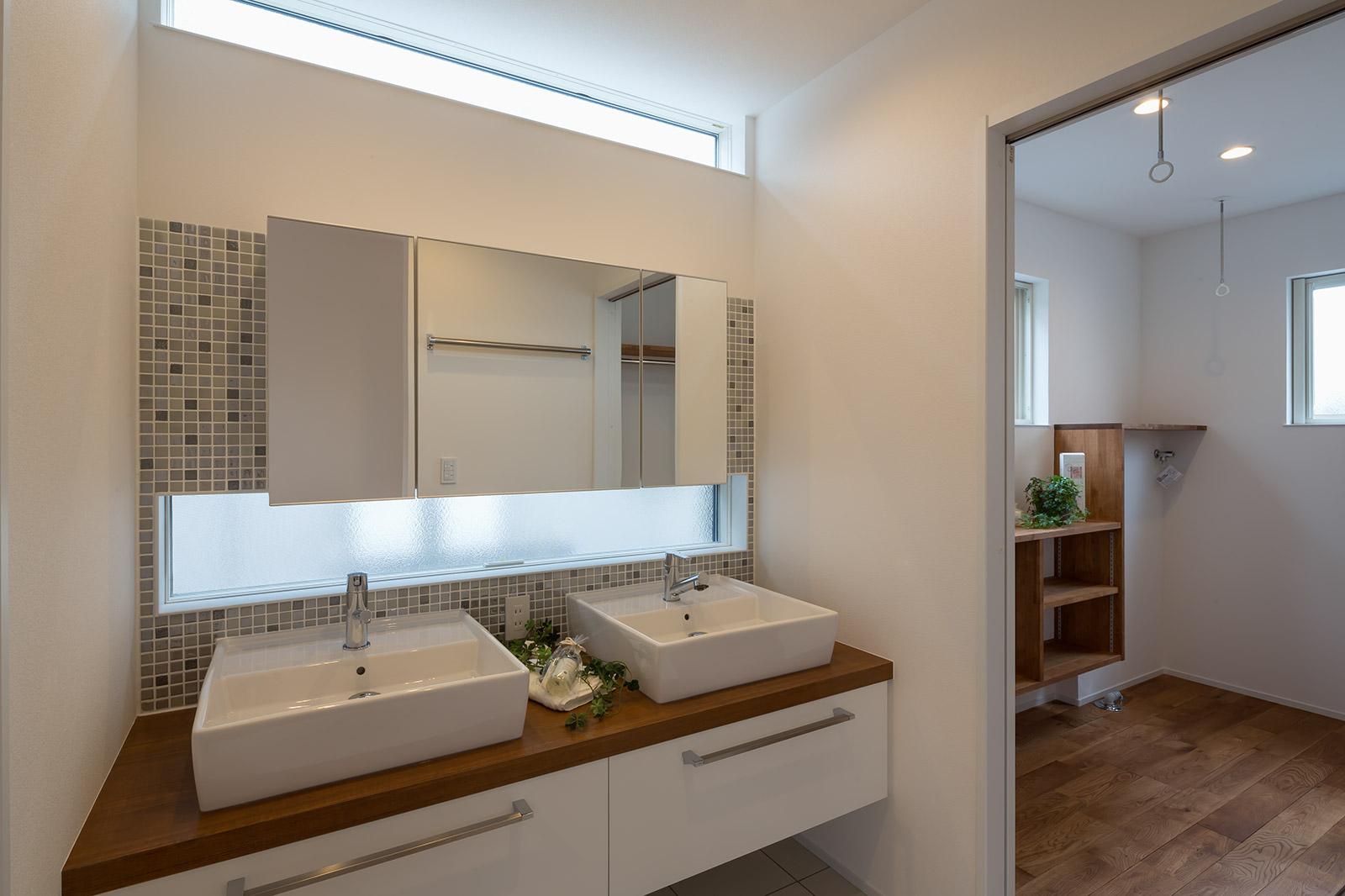 家族数に合わせて洗面台は2ボウルに。水まわりは親世帯のリビングとは対角にい位置している