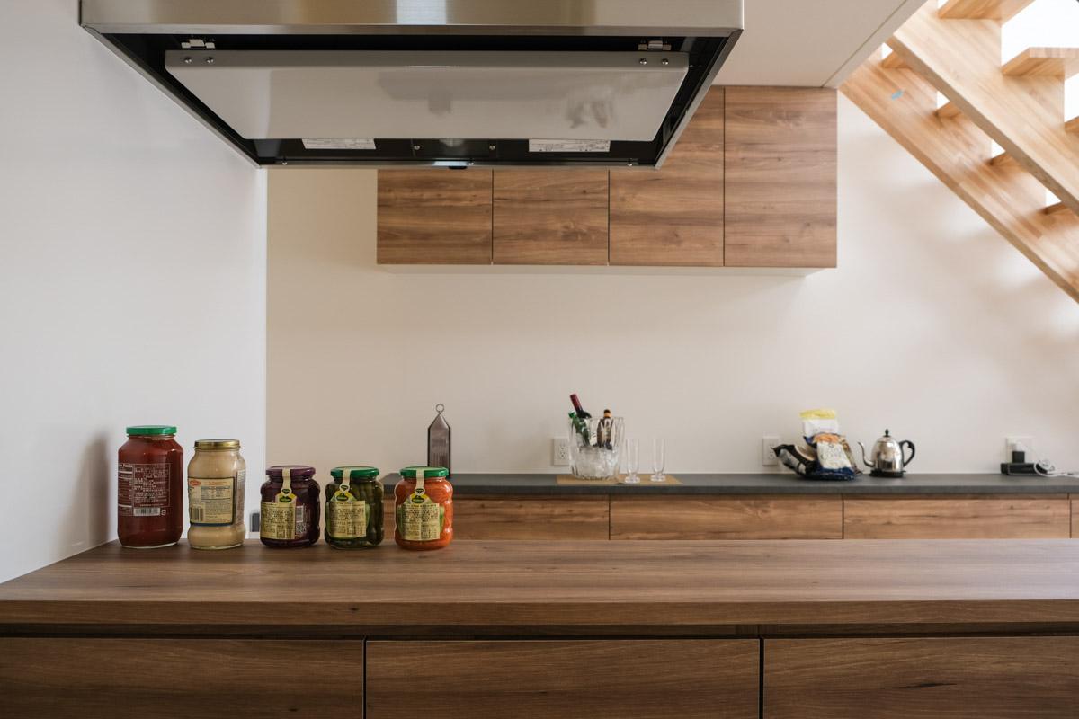 オープンなキッチンは、背面の造り付け収納に加え、前面腰壁収納もあるので常にスッキリ