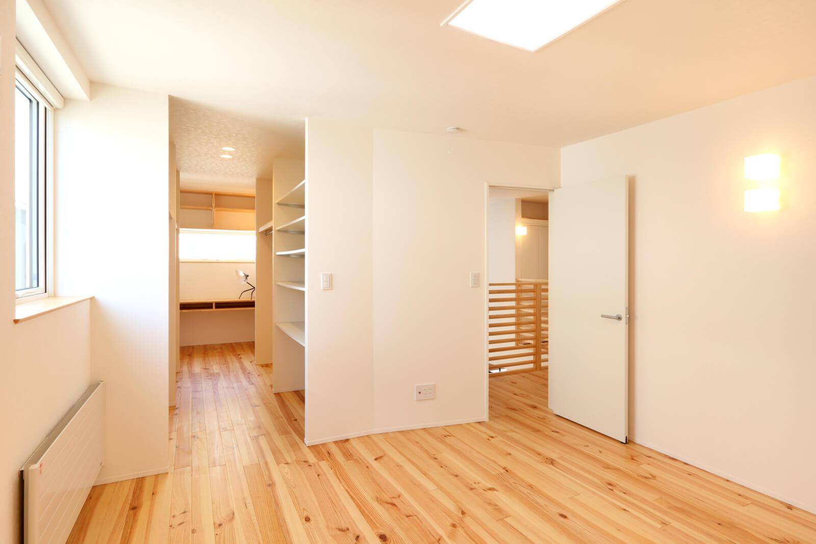 2階寝室と大容量のウォークインクローゼット。床材や壁材は家全体で同じ素材を使い、コストを抑えつつ見た目にも美しい仕上がりに。寝室のウォークインクローゼットの先には、あえて奥まった場所に設けた隠れ場のような書斎。ここにも収納がたっぷり