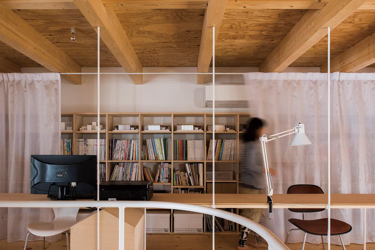 壁にはたくさんの本や資料がしまえる造作棚を設けた