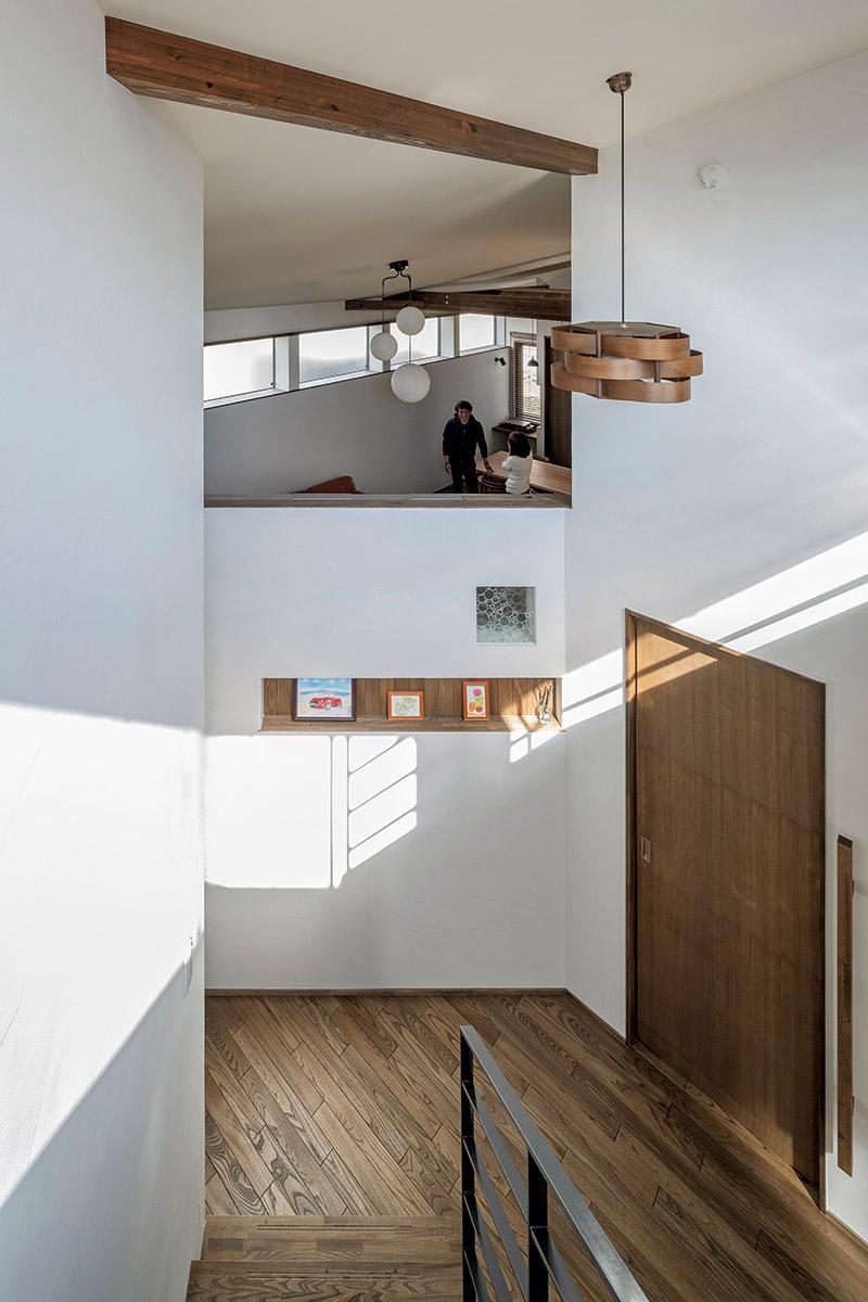 玄関前の壁上の空間を通じ2階からの光が1階の広間(写真奥)に届く。 Sさん宅の個性的な照明は主に奥さんのセレクト
