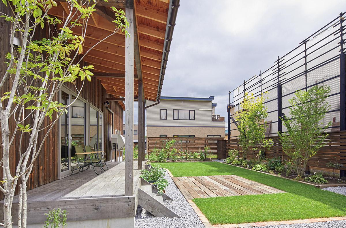 北海道ハウジングの提案で実現した、土間リビング直結のテラスはそのまま、この夏に完成した庭に続く。芝生中央には、バーベキューができるよう枕木を敷いた