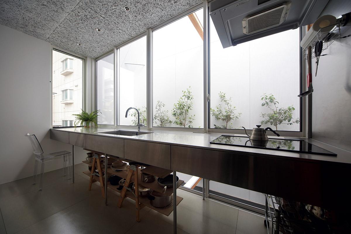 光井戸に面して設置されたオーダーメイドのキッチン。大きな窓の外にはプランター植栽の緑が揺れて気持ちがいい