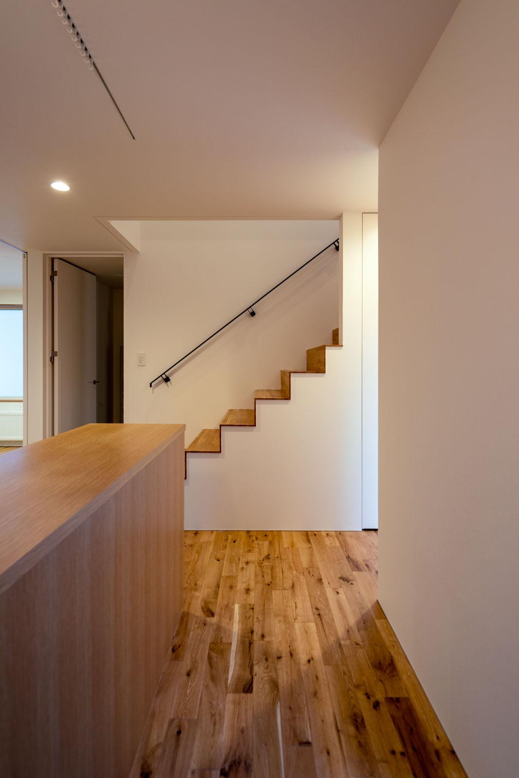 高さを抑えた造作収納で動線を分離し、広がり感を演出した玄関ホール