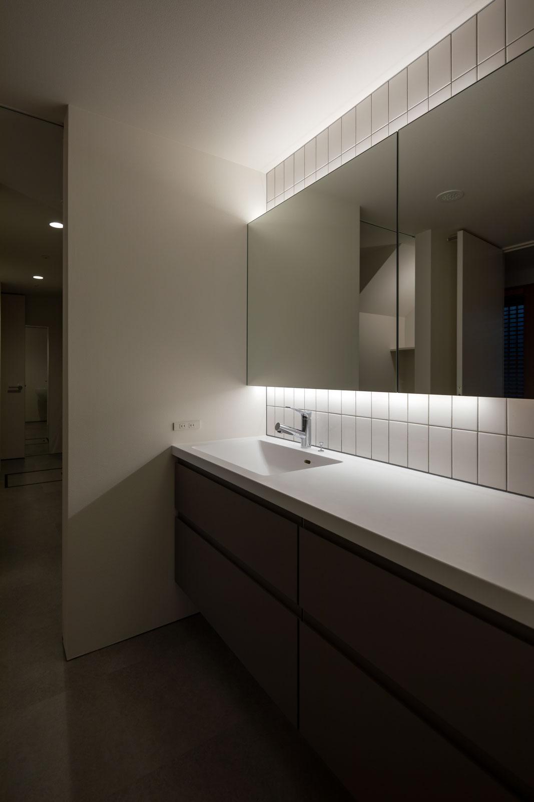 間接照明と大型ミラー、タイルを用い、すっきりと仕上げた洗面台。洗面カウンターには、メンテナンスのしやすい人工大理石を採用