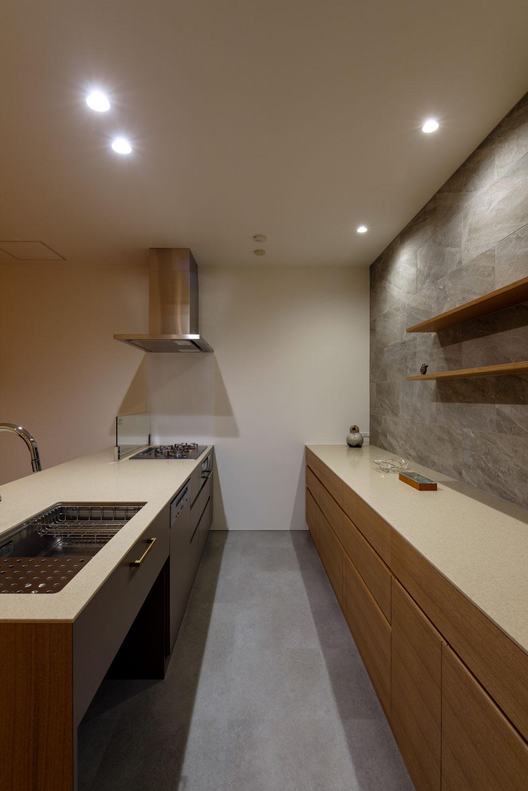 タモの面材とタイルを用いた奥さんこだわりの造作キッチン。シンク下にゴミ箱スペース、食洗機も組み込まれ、収納力も抜群。使い勝手と美しさを兼ね備えたキッチンは、くつろぎ空間の主役に