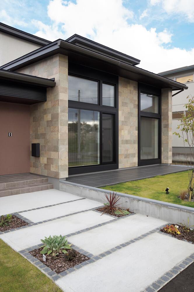 窯業系サイディングをベースに、玄関まわりは左官塗り、リビングまわりには石をあしらった変化に富んだ外観。アプローチに植えた南国を思わせる樹種や、リビングの大きな窓でリゾート感を演出した。リビング前には、最近流行りのアウトテラスも完備