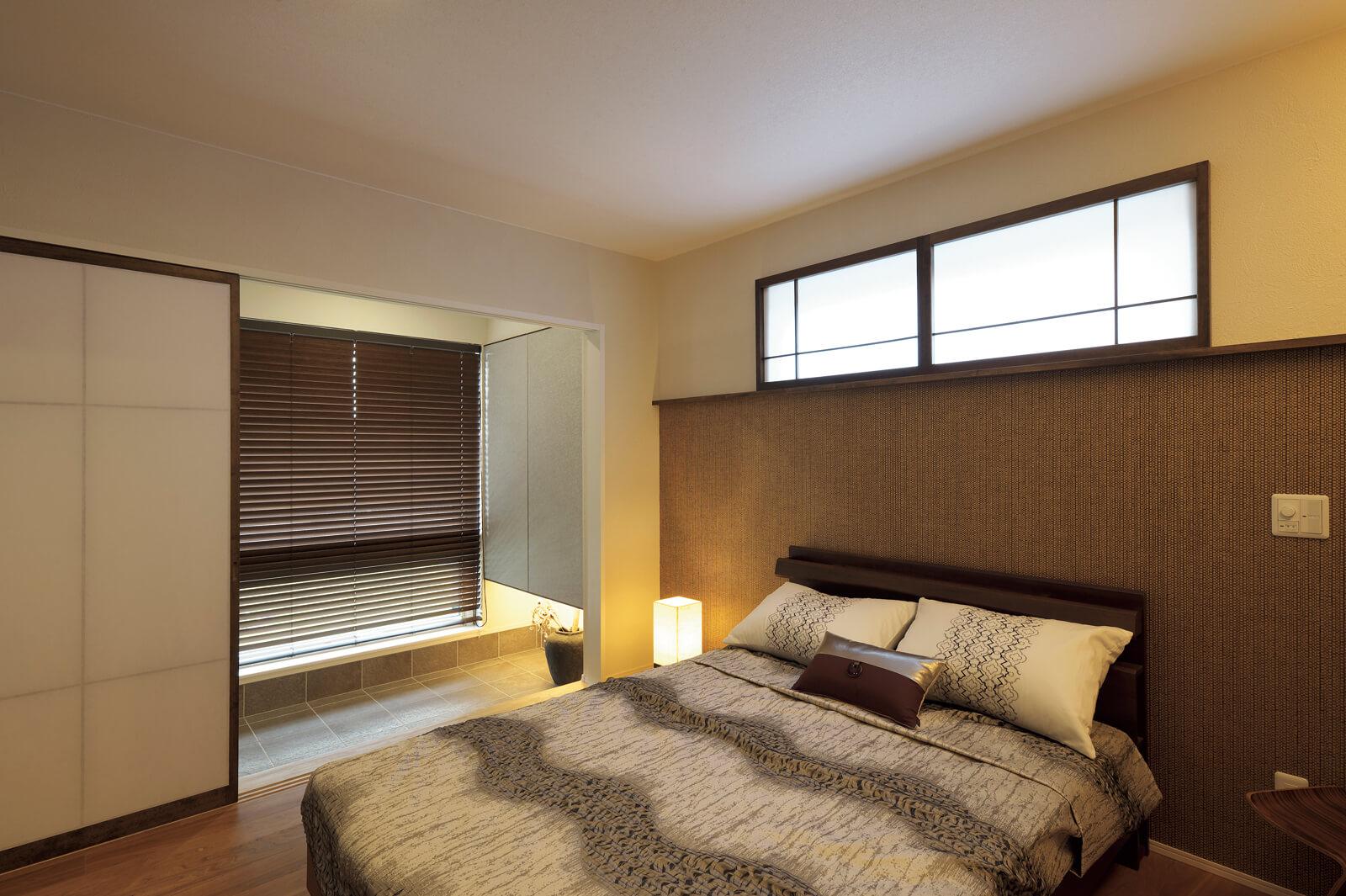 寝室は、心和む暖色系の間接照明とブラウン系の落ち着いた内装でまとめ上げたシックな空間。ベッドの上から眺める土間の風景にホテルライクの上質感が漂い、ワンランク上の癒しや非日常のくつろぎを感じられる