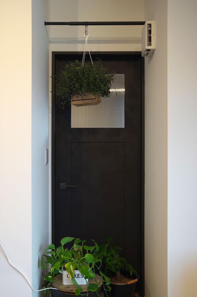玄関土間からリビングにつながるドアは薪を運び入れるために設けた。薪を置けるように床はタイルにしている