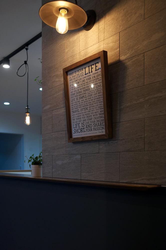 キッチン前の壁面はDIYで「エコカラット」を貼った。ブラケットライトがアンティークな雰囲気を醸し出す