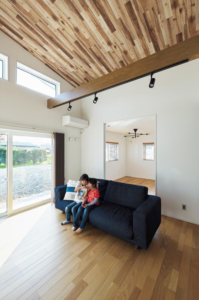 空が見える高窓が家族のお気に入り。リビングは、子供が大きくなったら薪ストーブを設置することを前提に考え、煙突と薪置き場、天井は汚れが目立たないクロスを選んだ