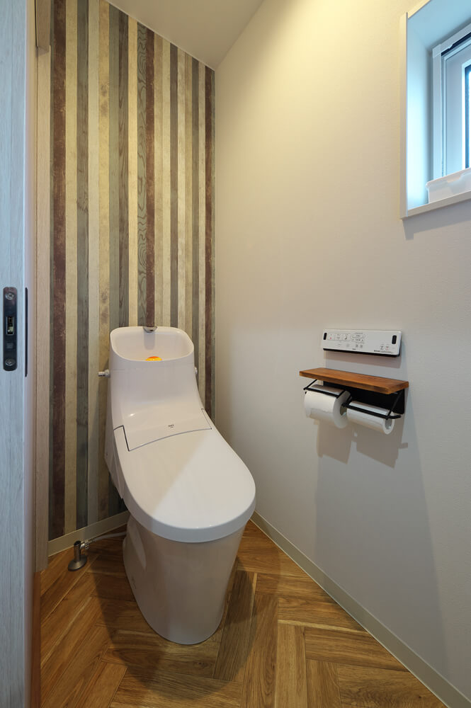 ヘリンボーンの床とデザインクロスなど、遊び心満載な洗面脱衣室側のトイレ