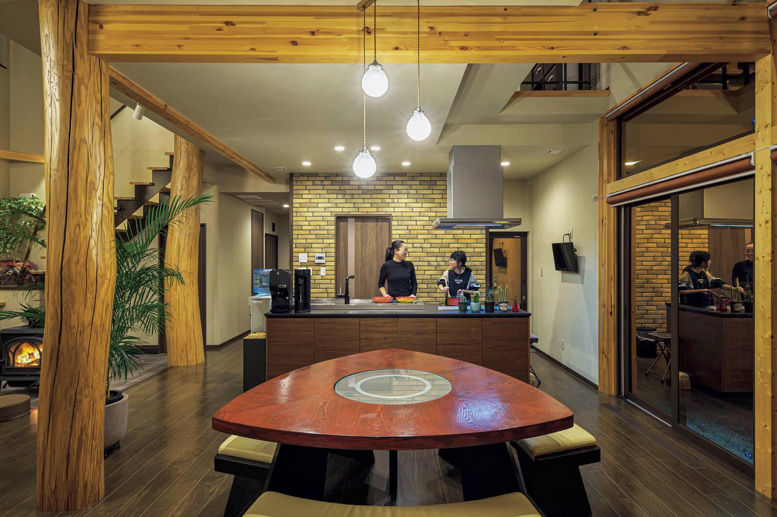 キッチン壁は外壁材を用いて重厚感を演出。天然木仕上げのシステムキッチンがナチュラルでラグジュアリーな雰囲気に似合う。後ろには、食品庫を設けているので家事導線も便利で使いやすい