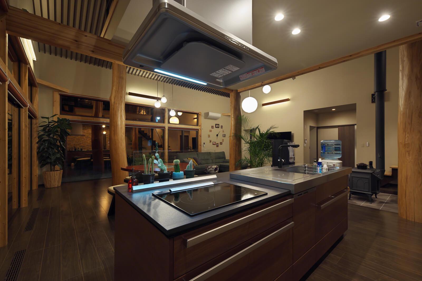 「セラミックと天然木による重厚感のあるデザインに一目ぼれしました。キッチンからはリビングと外の風景を一望でき、開放感も抜群です」と奥さん。キッチンの後ろには、食品庫を設けているので家事導線も便利で使いやすい