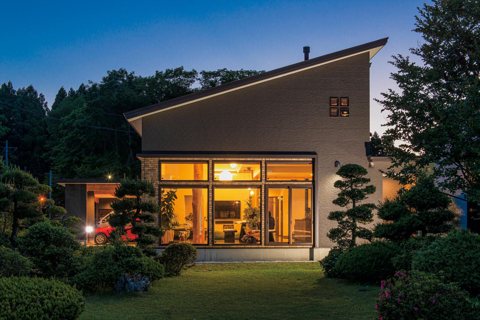 敷地南面から見るSさん宅の夕景。温かな照明の中に丸太柱が現れ、幻想的なムード。欄間窓にはあえてカーテンを付けず、周囲の目を楽しませている