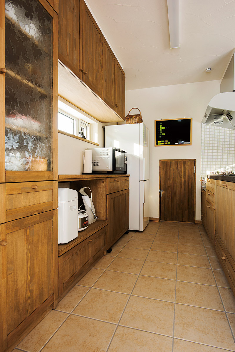 キッチンの食器棚には、Nさん所有のレトロな型押しガラスをはめ込んで。正面の扉は、階段下を利用した食品庫