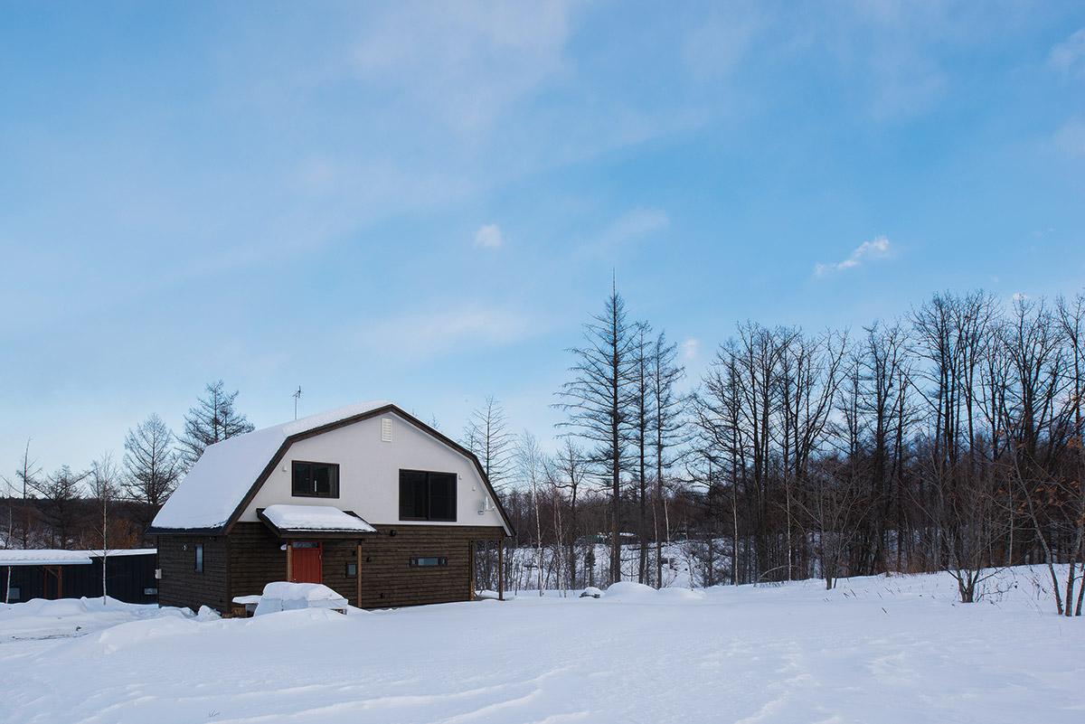 雑木林が点在する丘陵地に建つNさん宅。マンサード屋根が古きよき時代の田園住宅を思わせる