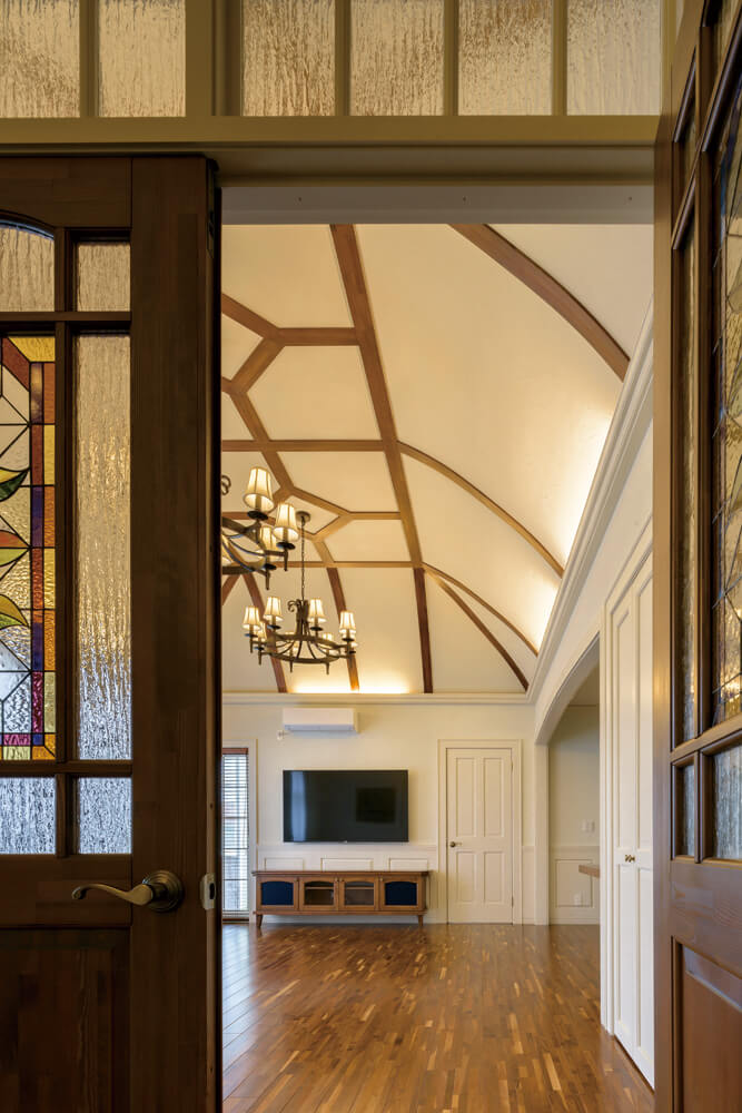 玄関のステンドグラス越しに広がるドーム型天井を備えた重厚なリビングには、海外で仕入れたシルク生地のカーテンやクラシックなシャンデリアをコーディネート