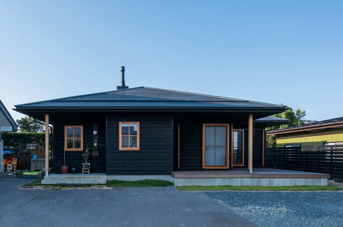 木外壁で仕上げた三角屋根の平屋。屋根に突き出た薪ストーブの煙突もデザインのアクセントに