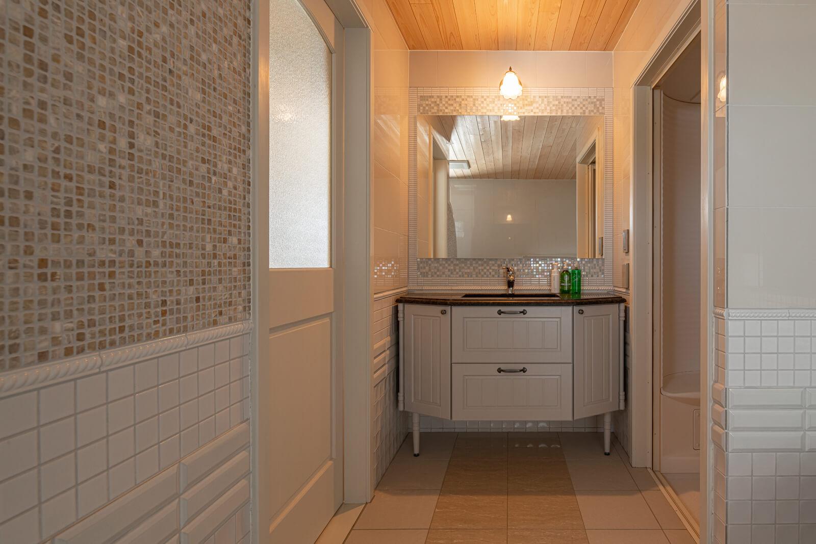 バスルームの入り口には、大理石を配した造作洗面台がある。右手は、シャワールーム。ゆったりと設えた水まわりは暮らしにも潤いを与えて