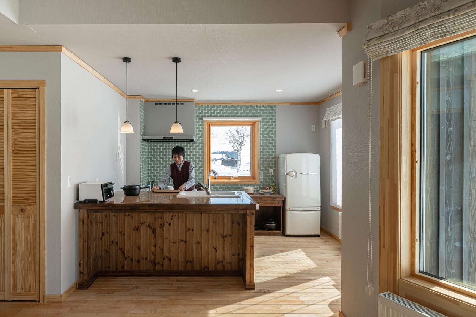 グリーンのタイル壁をアクセントにしたキッチンも、造作仕様。シンクやガス台は、奥さんの使い勝手が良い高さに調整した