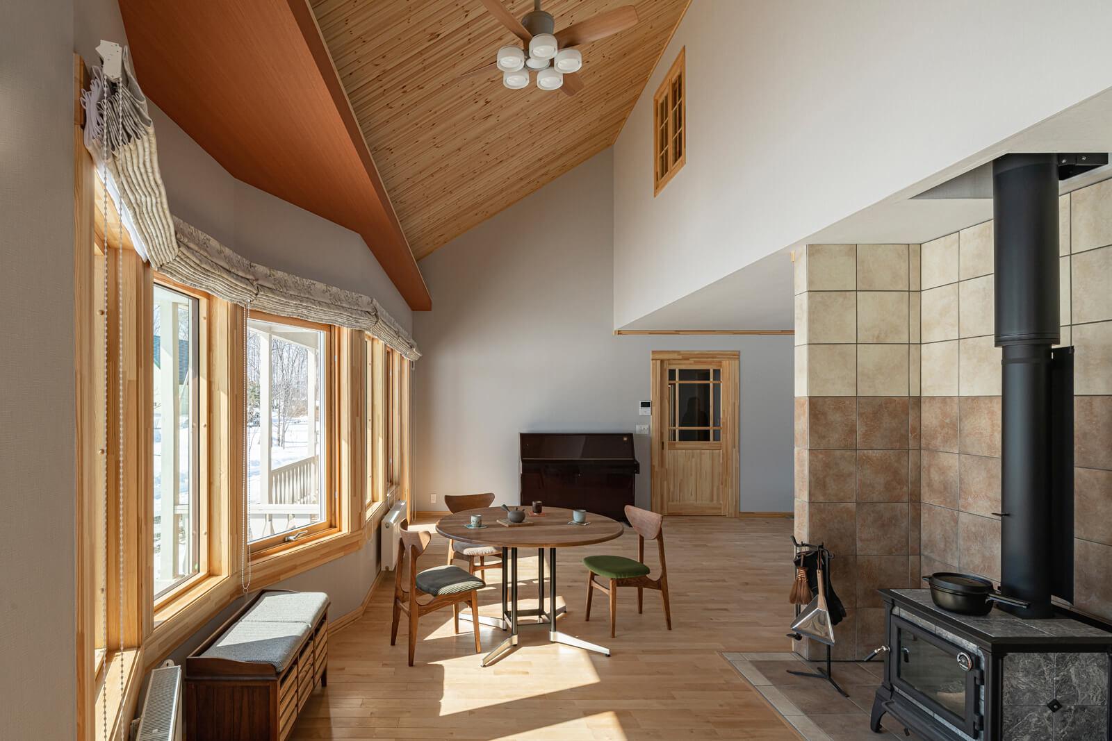 屋根なり天井が心地よい広がり感を演出するリビング・ダイニング。開口を連続して設けた眺めの良いLDKは、Aさんご夫妻のお気に入りのくつろぎスペースになった。壁に配したピアノは「子育ての思い出として」横浜から運んだもの