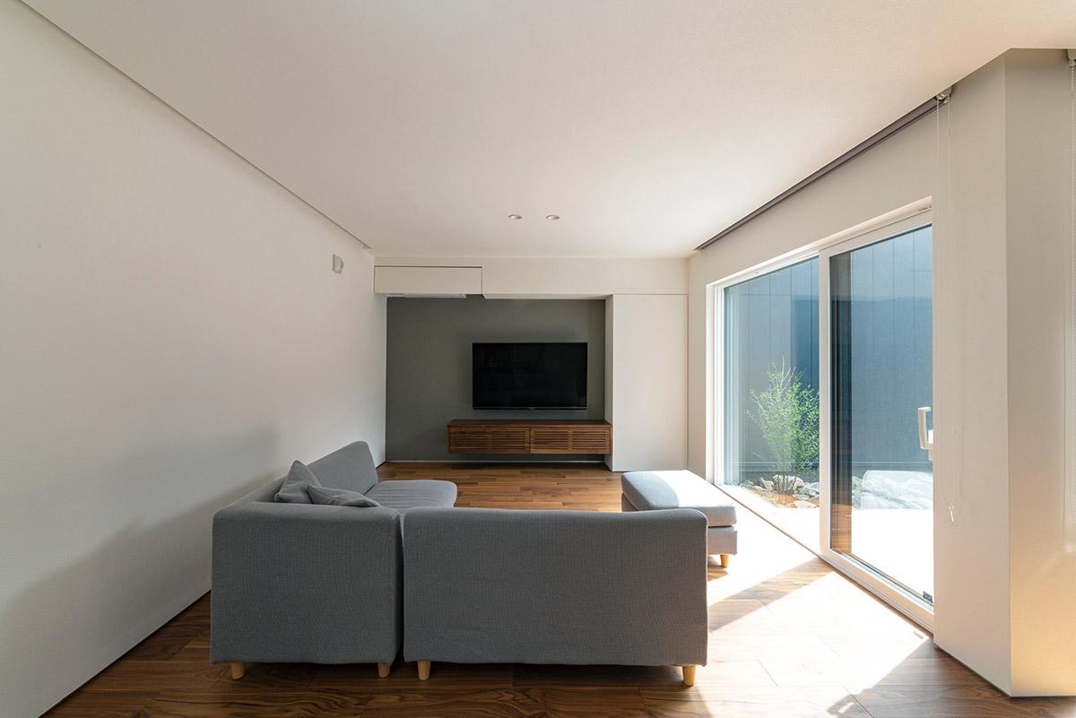 余計な装飾を排除したシンプルなリビング。大きな一枚ガラスの窓からソトにつながり、面積以上の広さを感じる
