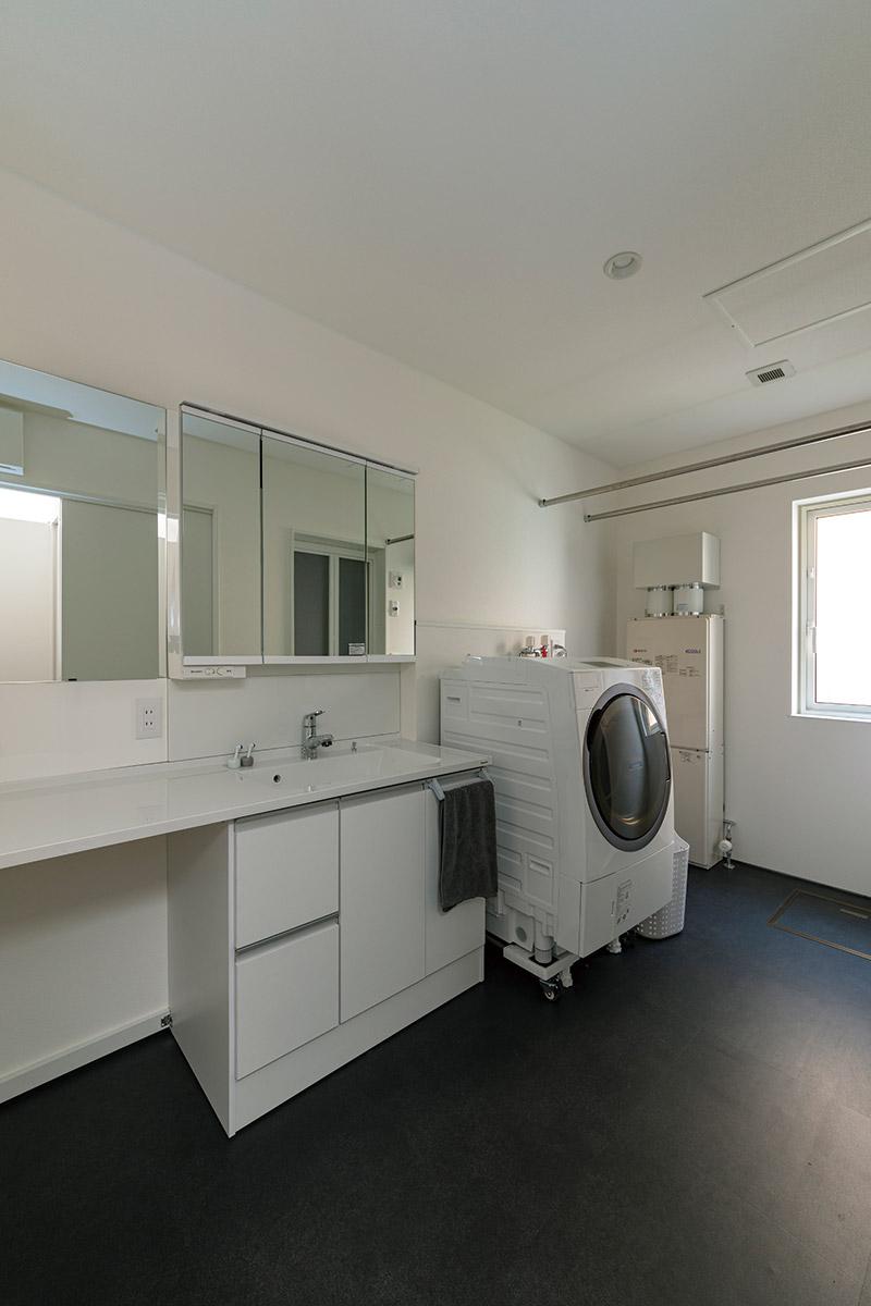床はマットな黒に仕上げ、造作や家電は白で統一したモダンなユーティリティ
