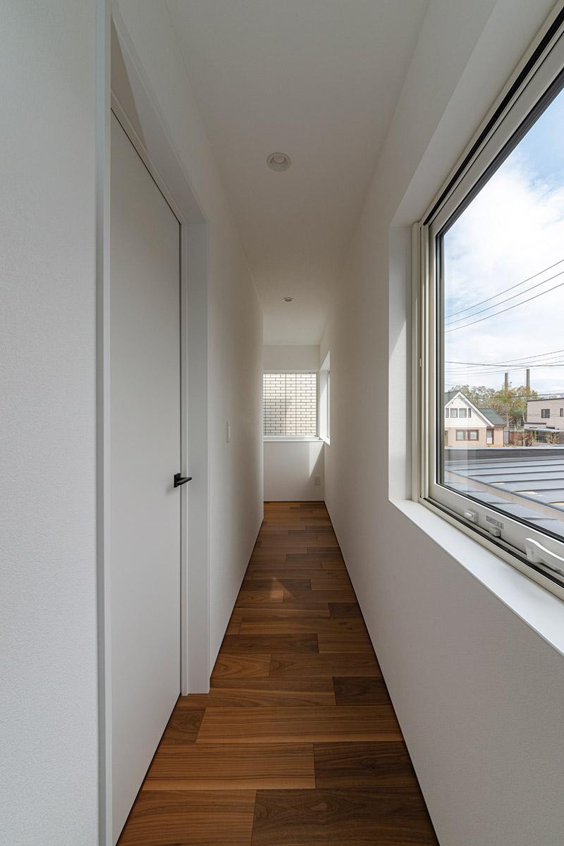 2階の廊下も複数の窓からの採光で明るさを確保。白壁に反射する柔らかな光の陰影がちょうどよい