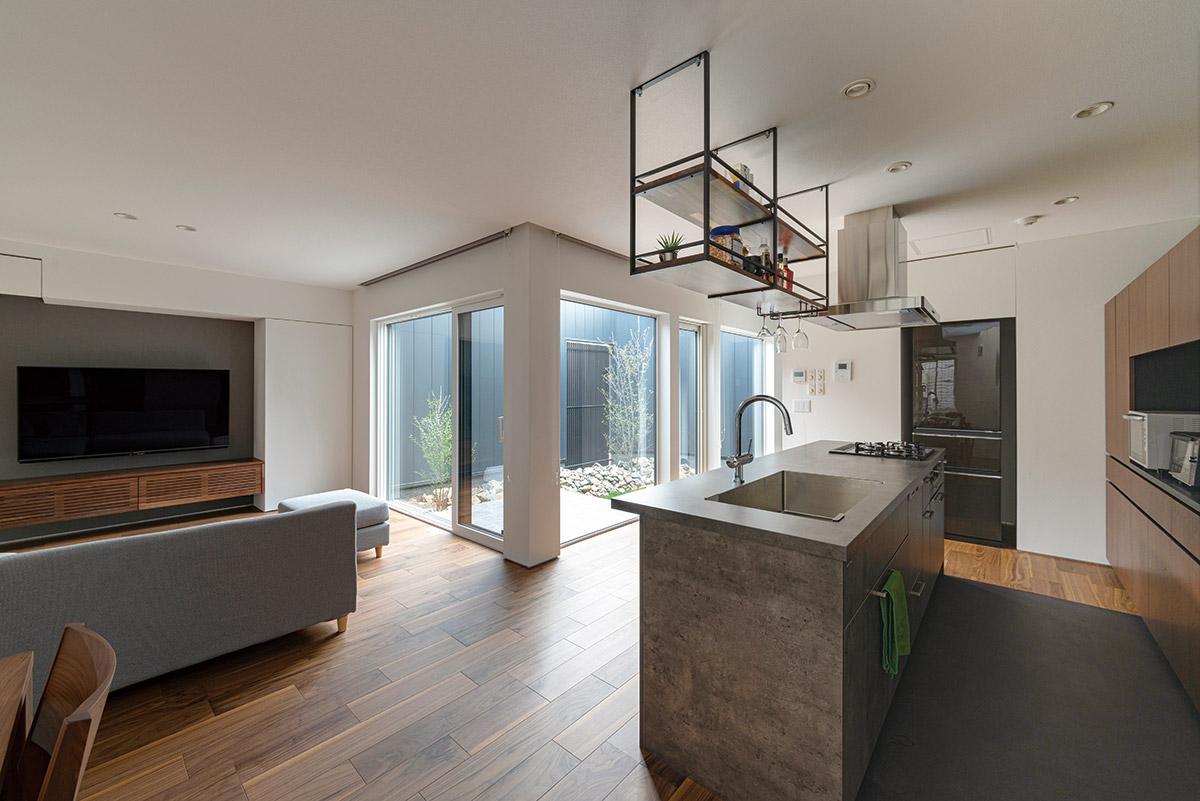 L字に配置されたキッチンとリビングは、どちらからも中庭を望める。外からの視線は遮りつつも絶妙の開放感