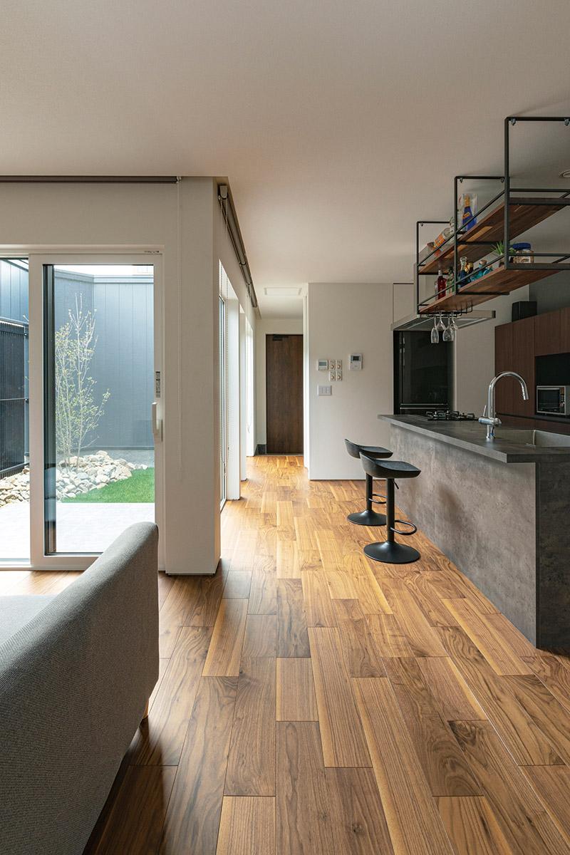 玄関からは仕切りや廊下をつくらず動線と空間を効率化。無垢板の化粧フロアがまっすぐ伸びる