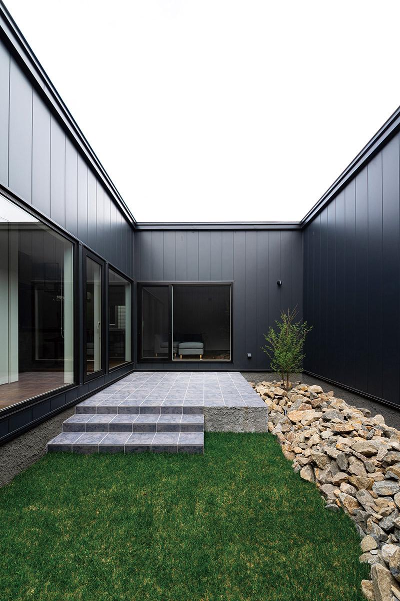 中庭は石タイル調のテラスと芝生、天然石、黒の外壁と塀で仕上げメンテナンスも簡単に。夜はライトアップして異なる雰囲気を楽しめる