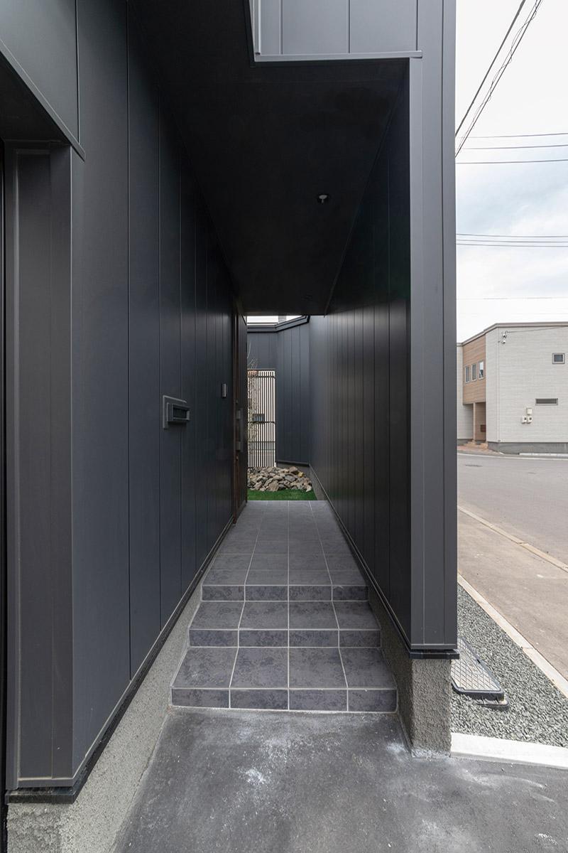玄関ポーチは出入りするところが見えないよう中庭の塀を伸ばして目隠し。そのまま庭にも入れる動線