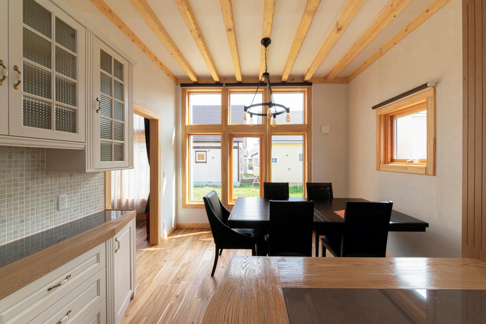 アメリカのクラシックな雰囲気が漂うダイニング・キッチン。白と白木を基調にした空間を、アイアンの照明やダークな色合いのダイニングセットが引き締める
