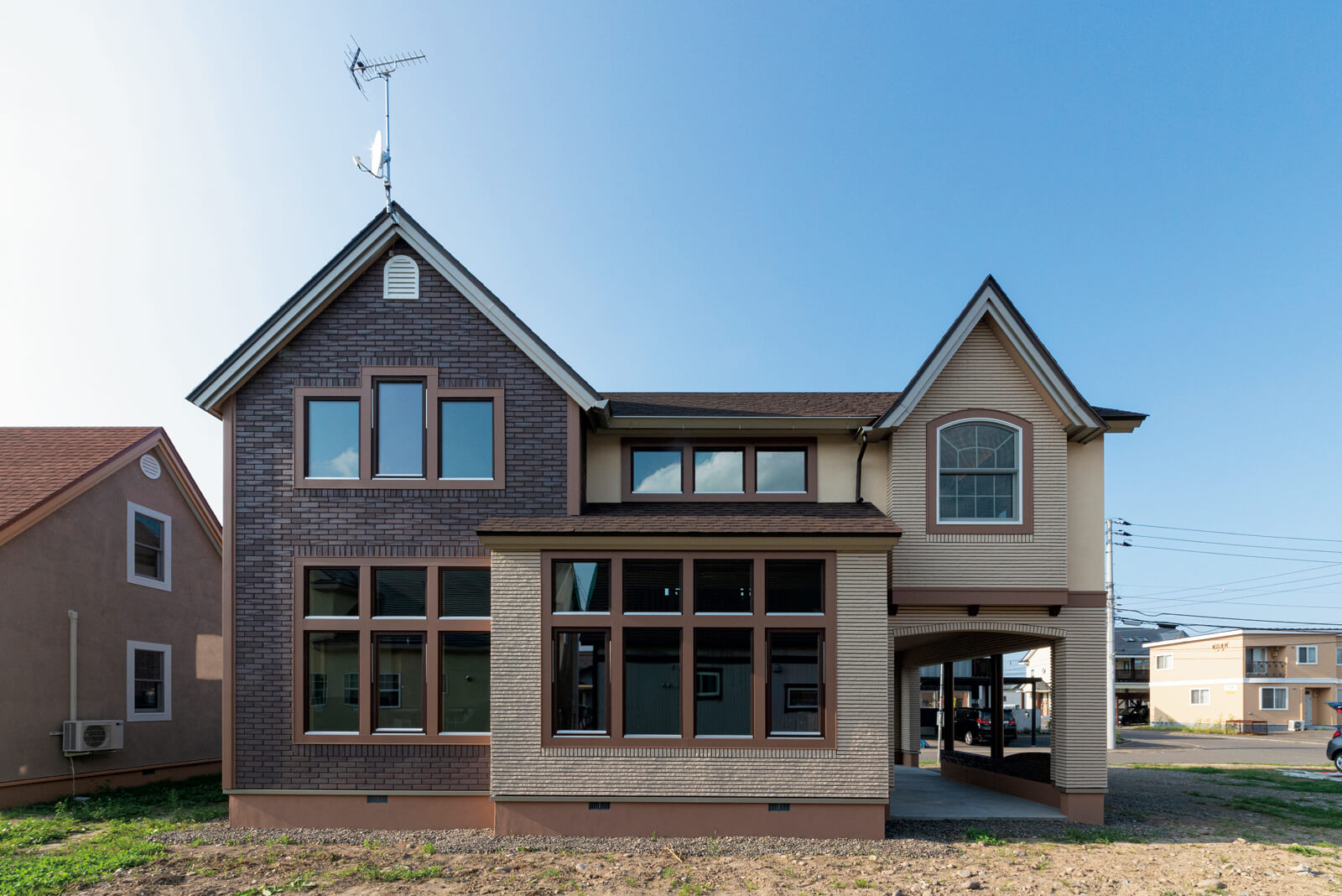 タイルを2色使いしたメンテナンスフリーの外壁と三角の小屋根が印象的な外観