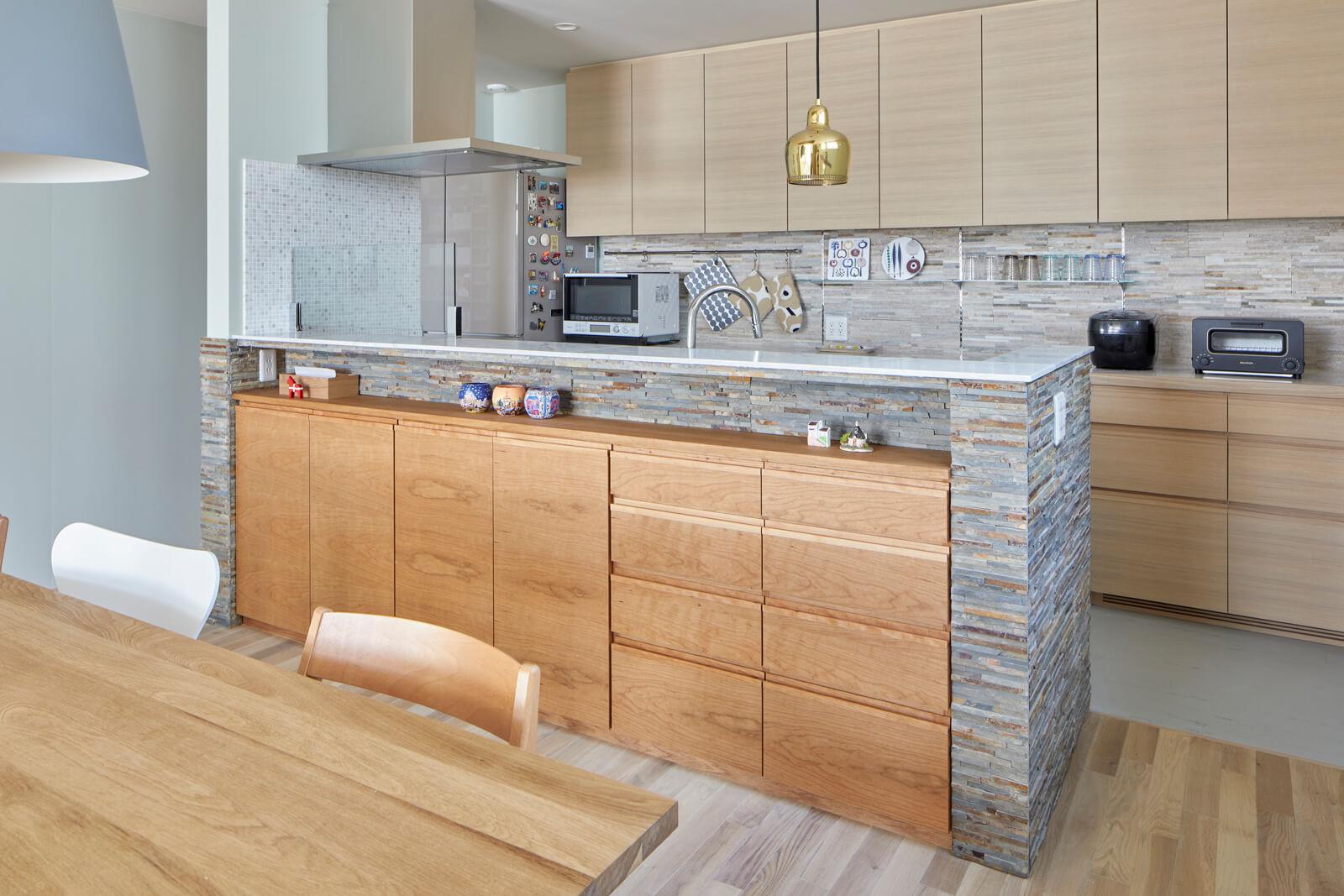 割り肌の石材を採用したキッチンは、建築家のアルヴァ・アアルトがデザインした真鍮のペンダントライトが映える。「北欧旅行時にアアルトの家を見て感動したことを澤田さんに伝えたところ、このペンダントライトを提案してくれました」