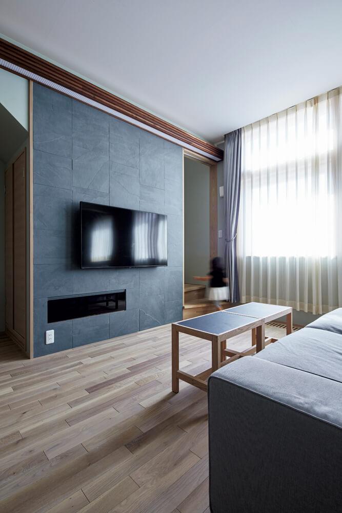 テレビ背面の壁は、マットグレー系の石材をセレクト。機器を収納する扉はブラッグガラスで制作した