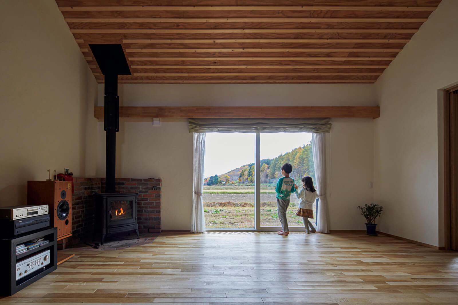 ナラの無垢床とリブ天井、珪藻土を採用したリビング・ダイニングは自然の温もりたっぷり。窓からは、Yさんが好きな十勝岳連邦最北のオプタテシケ山も見える